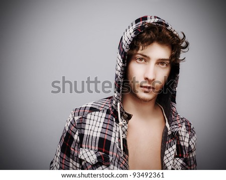 Confident young man posing and looking at camera. Curly hair, wearing a hoodie, studio shot. - stock photo