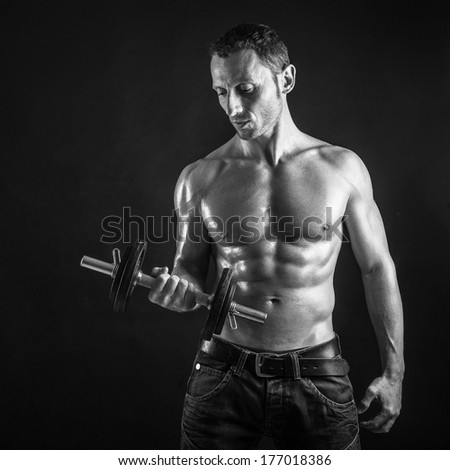Confident young man shirtless portrait training with dumb-bell, black and white image. - stock photo