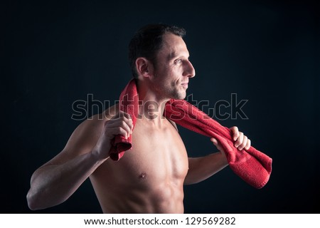 Confident young man shirtless portrait with red towel against black background. - stock photo