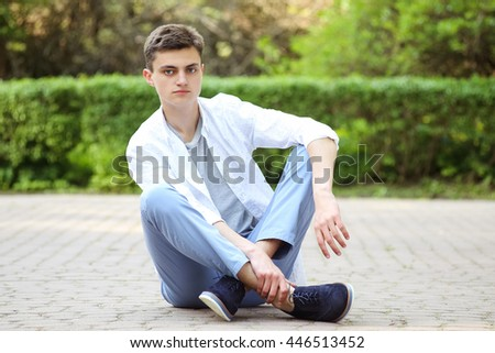 Confident young man sitting on a path in a park. A man in a white shirt and blue canvas trousers. Street fashion look, summer outfit