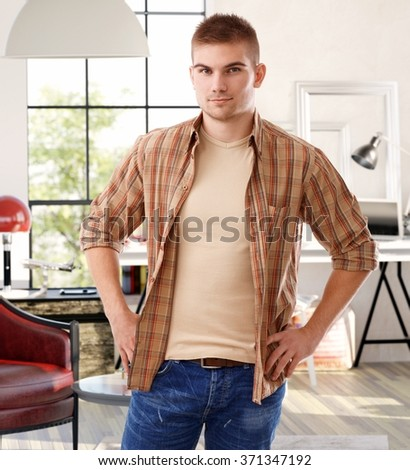 Confident young man standing at home with hands on hip, looking at camera. - stock photo