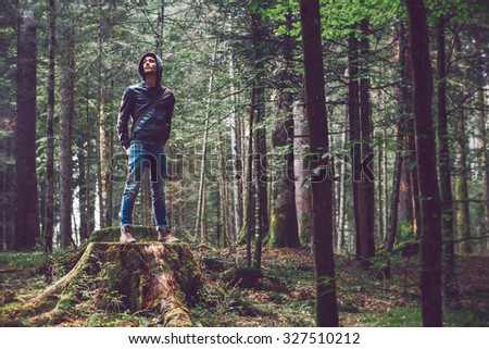 Confident young man standing in the forest, freedom and individuality concept
