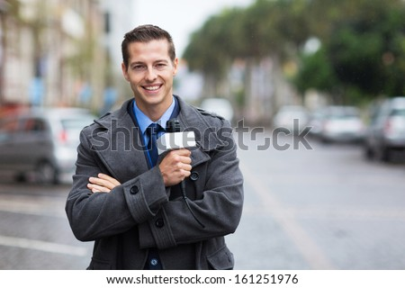 confident young news reporter working outdoors in the rain - stock photo