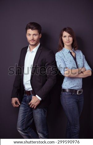 Confident Young Professional Couple in Semi-Formal Outfit Leaning Against Dark Gray Wall Background and Staring at the Camera. - stock photo