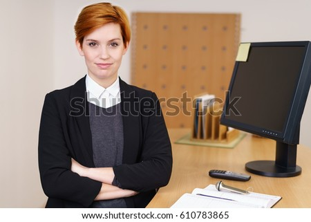 Confident young receptionist behind front desk stock photo confident young receptionist behind the front desk in a corporate enterprise or hotel standing with folded sciox Images