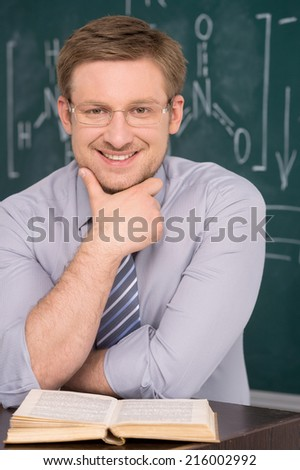 confident young teacher and classic chalkboard background. fine image of young caucasian teacher at school - stock photo