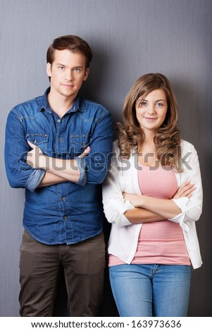 Confident young teenage couple posing side by side with folded arms against a dark grey background - stock photo