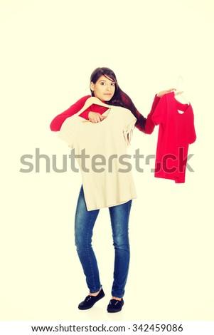 Confident young woman choosing shirt. - stock photo