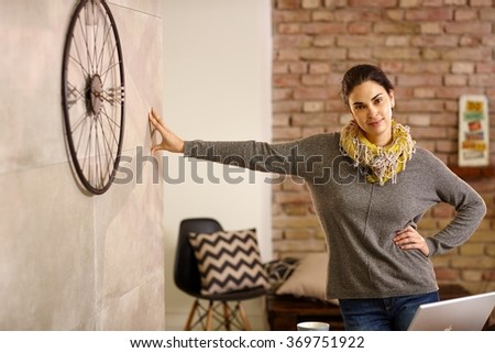Confident young woman leaning against wall at retro home, smiling, looking at camera. - stock photo