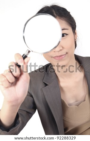 Confident young woman looking through a magnifying glass isolated (blank space for text) - stock photo