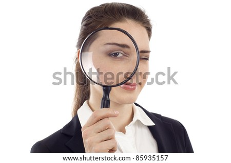 Confident young woman looking through a magnifying glass isolated over white background