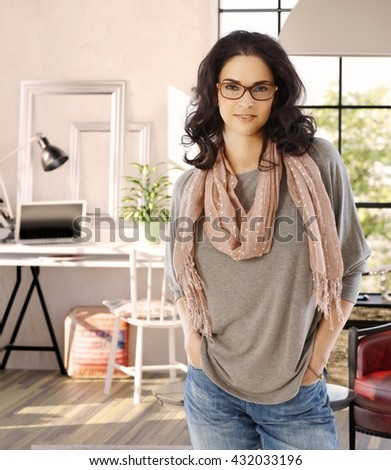 Confident young woman smiling at home with hands in pockets, looking at camera. - stock photo