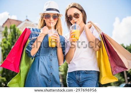 Confident young women in sunglasses with shopping bags drinking juice while standing in the park. Front view. - stock photo