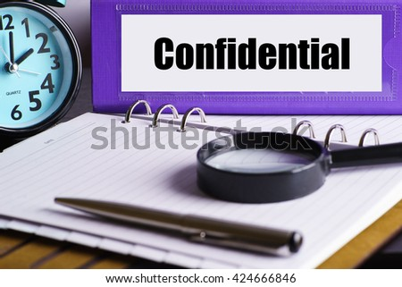 Confidential - Purple Office Folder on Background of Working Table with Magnifying glass,  a pen and clock - business and finance concept - stock photo