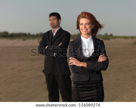 confindent young businesswoman and businessman, on a desert beach, looking on the hirizon
