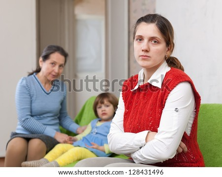 Conflict between generations. Sad young woman against grandmother and child