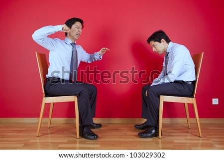 Conflict between two twin businessman sited next to a red wall - stock photo