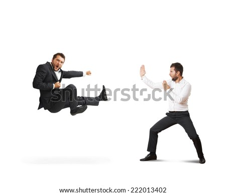conflict between two young businessmen. one man in suit is kicking, second man standing in karate pose. isolated on white background - stock photo