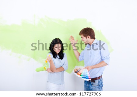conflict couple paint in green color white wall of their new apartment home, relationship problem, negative emotion, aggressive man scream on woman - stock photo