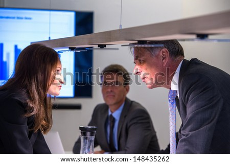 Conflict in office : Female business executive arguing with her boss at meeting over latest sales figures with others watching - stock photo