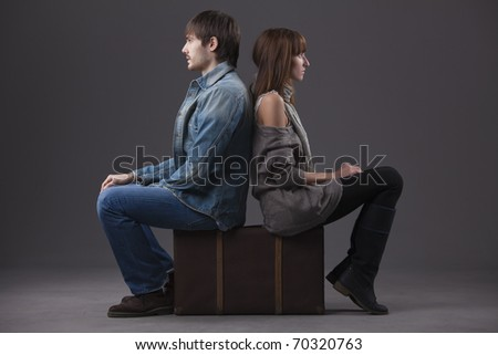 conflict in relationship - man and woman sitting on suitcase back on back - stock photo