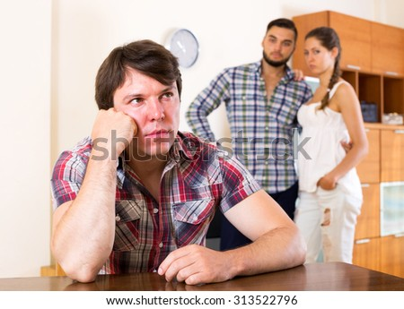 conflict in young polygamous couple indoors in the living room - stock photo