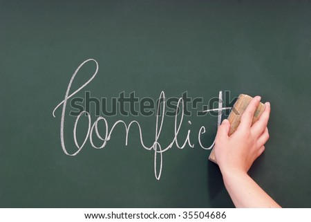 conflict written in a blackboard to be removed with an eraser - stock photo