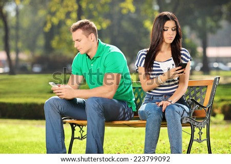 Conflicted couple not talking to each other seated on a wooden bench in park - stock photo