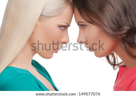 Confrontation. Two angry women standing face to face with their foreheads touching and looking at each other while isolated on white - stock photo