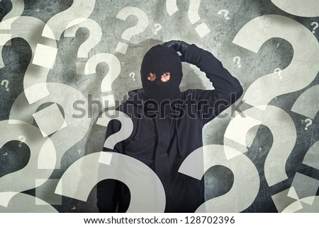 Confused burglar concept with questions marks, Thief with balaclava caught confused and without idea in front of the grunge concrete wall, computer generated question marks. - stock photo