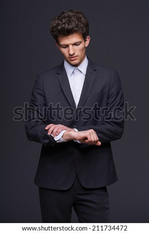 Confused business man looking on his wrist with no watch against dark background. - stock photo