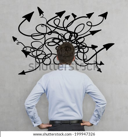 Confused businessman because of a huge variety of thoughts. Thinking about structuring business process and solutions. Arrows, different directions. - stock photo