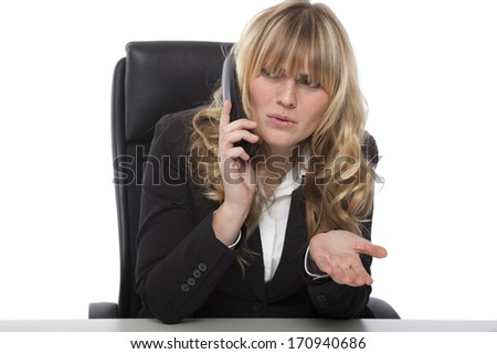 Confused businesswoman frowning as she chats on the telephone at work asking for clarity an a certain point while gesturing to show her bewilderment - stock photo
