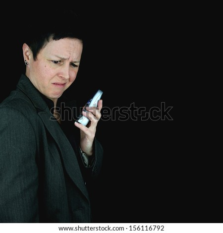 confused businesswoman listening to a telephone call. Isolated on black background. - stock photo