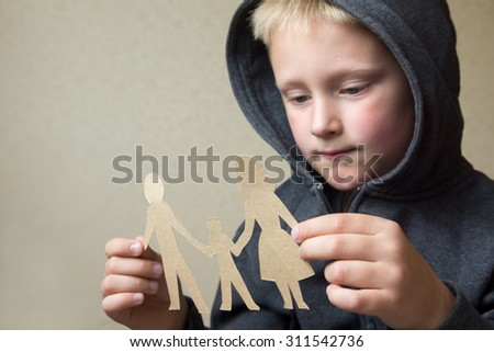 Confused child with paper family, family problems, divorce, suffer concept  - stock photo