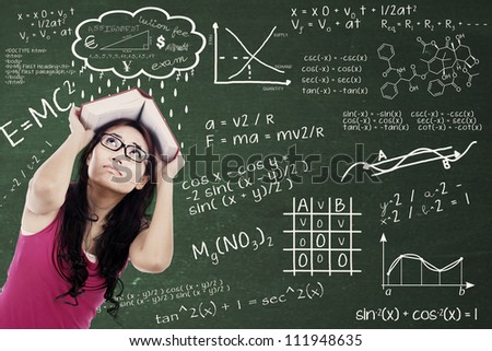 Confused college student with formulas on the blackboard and covering her head by textbook. shot at class