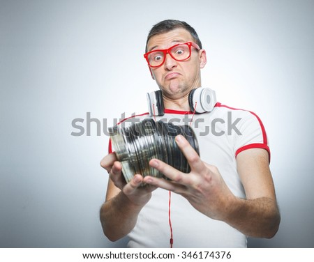 Confused dj holding a lot cds, isolated on gray. Facial expression. Funny party man looking astonished - stock photo