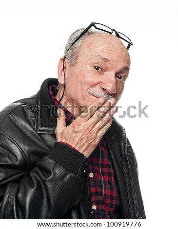Confused elderly man covers his mouth with his hand - stock photo