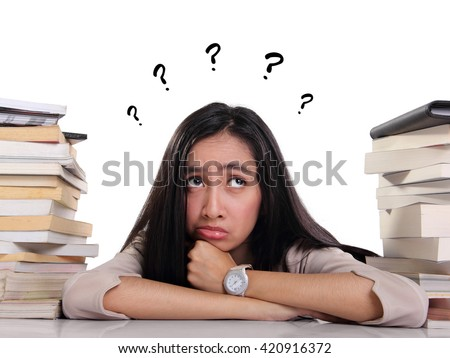 Confused female student laying between stacks of books, looking up with many question on her head, over white background - stock photo