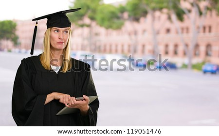 Confused Graduate Woman Holding Digital Tablet against a unversity building as a background - stock photo