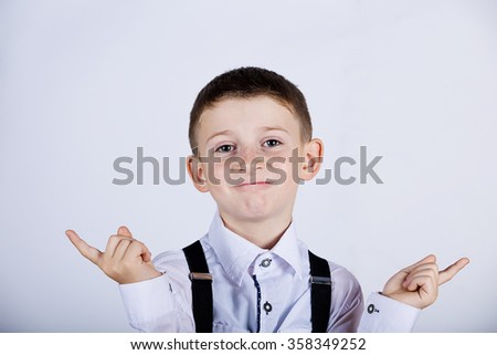Confused little boy gesture over grey background. - stock photo
