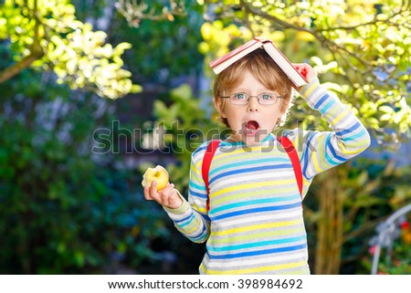 Confused little kid boy with glasses, books, apple and backpack on his first day to school or nursery. Child outdoors on warm sunny day, Back to school concept - stock photo