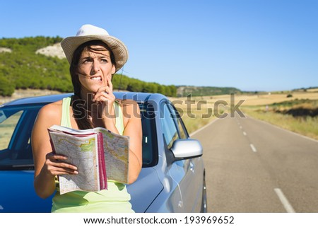 Confused lost woman on car roadtrip travel problem searching in road map. - stock photo