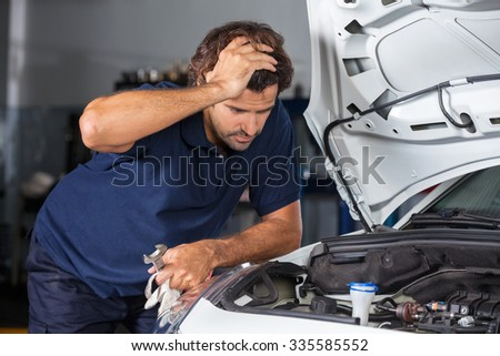 Confused male mechanic examining car engine at auto repair shop