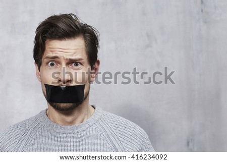 Confused man with tape over mouth, portrait - stock photo
