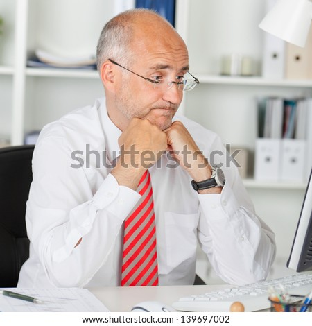 Confused mature businessman staring at computer while leaning on office desk - stock photo