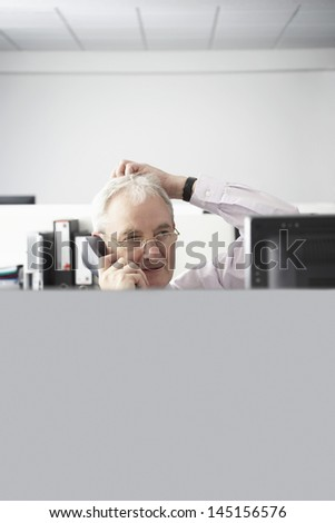 Confused middle aged businessman on call at computer desk in office - stock photo