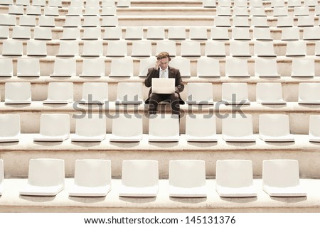 Confused middle aged businessman working on laptop while sitting alone in center of empty auditorium outdoors - stock photo
