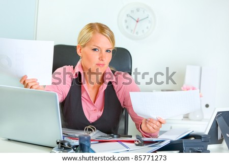 Confused modern business woman at office desk - stock photo