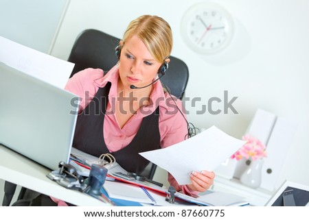 Confused modern female manager with headset at working place - stock photo